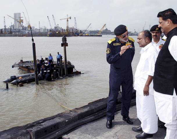 Indian Navy chief Admiral D.K. Joshi (foreground, L) talks with India's Defence Minister A.K. Antony (3rd R) as navy divers standing on the INS Sindhurakshak submarine prepare to dive into the waters of the Arabian Sea, during a rescue operation in Mumbai August 14, 2013. Joshi held out little hope for survivors on the submarine after some of its weapons detonated accidentally and fire swept through it.  Eighteen sailors were on board the 16-year-old Russian-built INS Sindhurakshak, which was docked at the main naval base in Mumbai when two blasts rocked the vessel in the middle of Tuesday night.     REUTERS/Indian Ministry of Defence/Handout (INDIA - Tags: MARITIME MILITARY POLITICS DISASTER) ATTENTION EDITORS – THIS IMAGE WAS PROVIDED BY A THIRD PARTY. NO SALES. NO ARCHIVES. FOR EDITORIAL USE ONLY. NOT FOR SALE FOR MARKETING OR ADVERTISING CAMPAIGNS. THIS PICTURE IS DISTRIBUTED EXACTLY AS RECEIVED BY REUTERS, AS A SERVICE TO CLIENTS